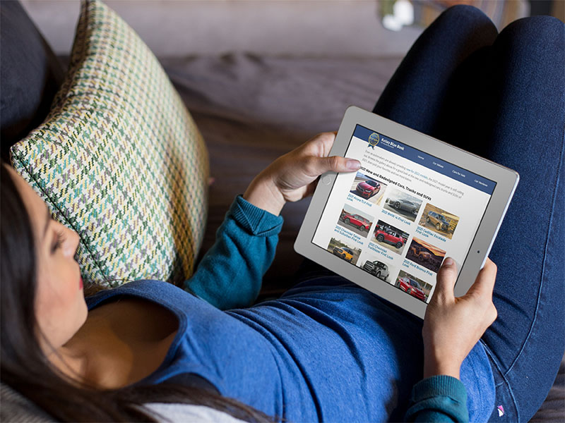 woman holding tablet shopping for cars